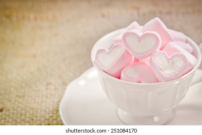 Valentines Day background with pinks hearts in a cup on vintage retro background.