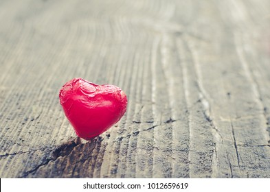 Valentines Day background with red chocolate heart shaped candy on rustic wooden table with place for text. Romantic love concept. Valentine's greetings card. Selective focus. Toned image. Copy space.