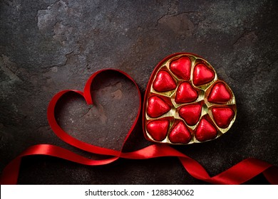 Valentines Day background with red heart and chocolate hearts. Heart shape from ribbons. Happy Valentine Day