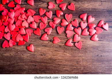 Valentines Day background with red hearts on a wooden table, top view. Red heart shaped candies on a wooden brown background. The concept of Valentines Day.