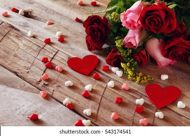 Valentines day background. Red hearts and roses on wooden table