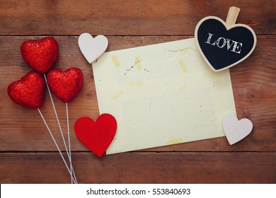 Valentines day background. Red hearts and empty letter on wooden background. Flat lay composition