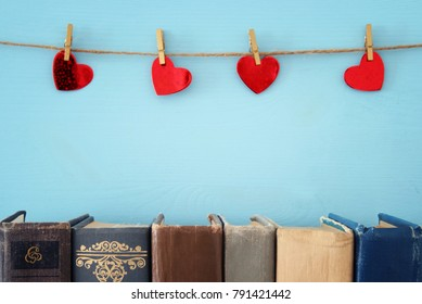Valentine's day background. Red hearts hanging over rope and old books