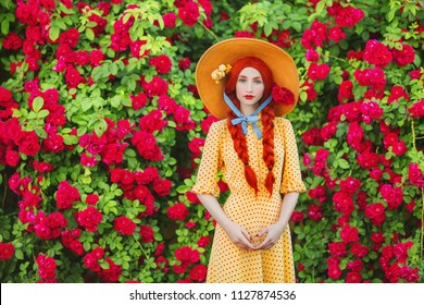 Valentines Day background. Retro girl with red lips in stylish yellow dress in dots in beautiful summer roses garden. Valentines Day beauty redhead model with plait on background of bush of roses.