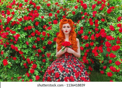 Valentines Day background. Retro girl with red lips in stylish dress with print of roses in beautiful summer garden. Valentines Day beauty redhead model with hairstyle on background of bush of roses.