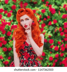 Valentines Day background. Spectacular girl with red lips in stylish dress with print of roses in beautiful summer garden. Spectacular beauty redhead model with hairstyle on background roses bush.