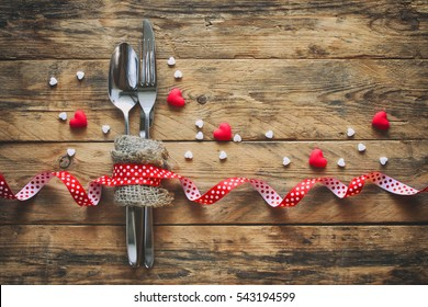valentine's day background, spoon, fork, knife, ribbon and small hearts on old wooden table, retro style