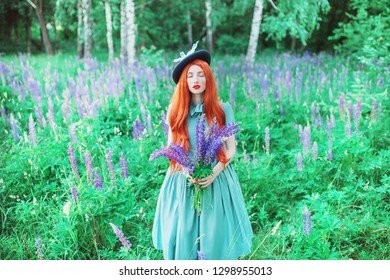 Valentines Day background. Spring blooming lupine flower garden. Perfect lady with red lips in dress. Summer hat. Perfect flower wall. Redhead lady on background of lupine garden. Valentines postcard