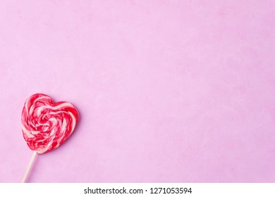 valentines day background, sweet love, heart shaped lollipop on pink backdrop. romance and celebration concept