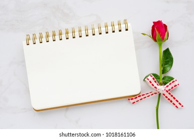 Valentine's day background, template, Red rose and blank notebook paper on white marble background with copy space for text, top view, flat lay