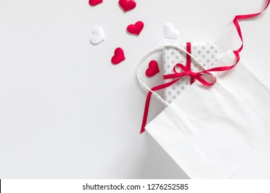 Valentine's Day background. White paper bag, red hearts and  gift on white background. Valentine day concept.