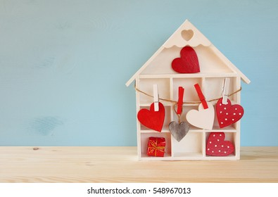Valentines day background. Wooden house with many hearts on the table