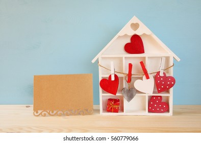 Valentines day background. Wooden house with many hearts next to letter on the table