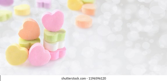 Valentines Day Banner: Pastel Candy hearts on a silver bokeh background with copy space.