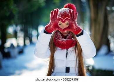 Valentine's Day Beautiful Fashion sexy Girl  making heart symbol with snowy hands Winter portrait of young beautiful woman wearing knitted snood covered in snow. Snowing winter beauty fashion concept.