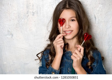 Valentine's Day. Beautiful girl in denim clothes with red heart lollipops.