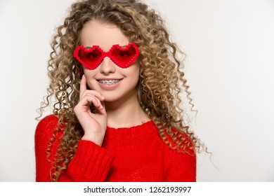 Valentine's Day. Beautiful girl in red sweater with  glasses hearts.