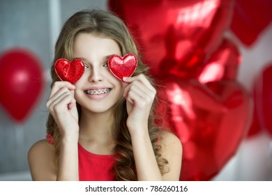 Valentine's Day. Beautiful girl red with heart balloons. Girl with braces. Orthodontics treatment.