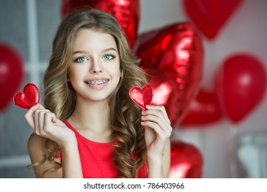 Valentine's Day. Beautiful girl in red dress with heart balloons. Girl with braces. Orthodontics treatment.