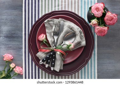 Valentine's day, birthday or anniversary table setup, top view on greybackground. Pink roses, dark red plates, napkin and crockery, decorated with rose bud and ribbons.