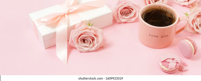 Valentine's day, birthday background banner. Pink cup of coffee, pink roses and pink macaroons on pink background. Copy space