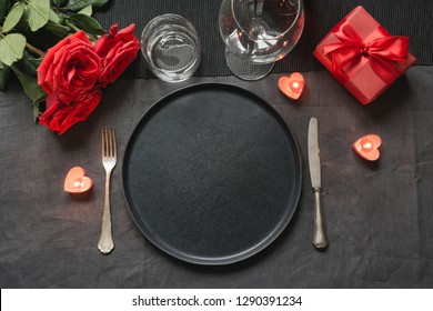 Valentine's day or birthday romantic dinner. Elegance table setting with red rose on black linen tablecloth.