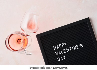 Valentine's day. Black letterboard with quote Happy Valentine's Day, and glass of rose wine on pink background.