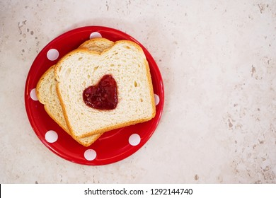 Valentines day breakfast in bed  sandwich with red jam hearts coffee cookies on a white trayon red plate, overhead view