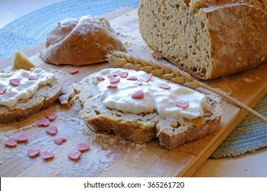 Valentine's day breakfast with bread with seeds sour cream and heart shaped sugar beads in landscape side crop