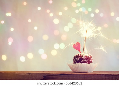 valentine's day cake with heart and sparkler, blurred light effect, retro style