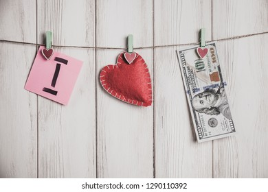 Valentines day card. Heart and sheets of paper on rope with words of love on old white wood background