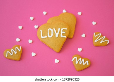Valentine`s Day card, homemade shortbread cookies in heart shape with LOVE message and white candy confetti on pink background. Love and romance concept.