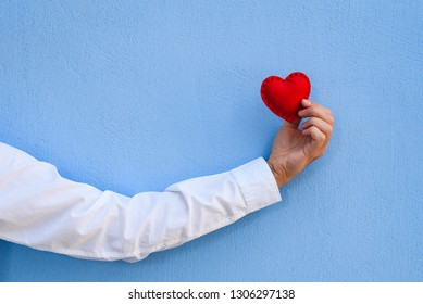 Valentine's day card. The red heart in the guy's hand against the background of the blue wall. Сopy space for greeting or advertising text