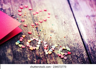 Valentine's day card with small hearts on wooden background and word