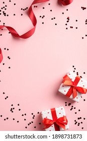 Valentines day card template with gifts, red ribbon, confetti on pink background. Flat lay, top view, copy space.