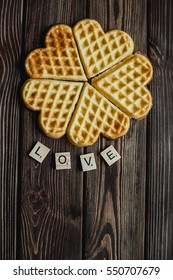 valentines day card. text love and heart shape waffles on brown wood background
