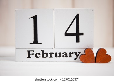 Valentines Day card with wooden block calendar on white wooden background and hearts