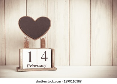 Valentines Day card with wooden block calendar on white wooden background witn copy space for text.