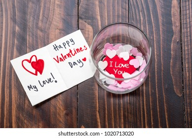 Valentines Day cards greeting. Happy Valentines day my love and I love you and mini heart shaped paper in bottle on brown wooden table.