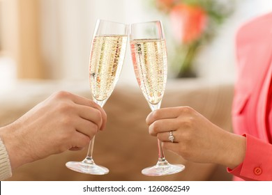 valentines day, celebration and engagement concept - close up of couple hands clinking champagne glasses