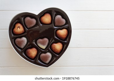 Valentines day chocolate candy heart box on white wooden table with copy space