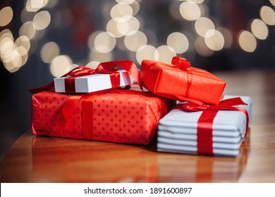 Valentine's Day, Christmas and New Year presents concept. A pile of gift boxes on the table at a cafe. A stack of presents on a wooden surface at a restaurant. New normal and winter holidays