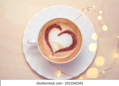 Valentine's Day coffee in bed with a pattern of hearts made from cinnamon