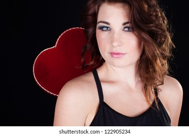 Valentine's Day comes to a beautiful woman holding a heart behind her