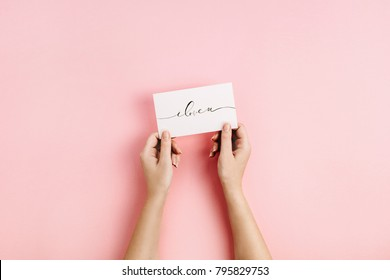 "Valentine's Day composition. Female hands holding card with calligraphic quote ""I Love U"" on pale pink background. Flat lay, top view Love concept."