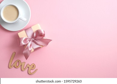 """Valentine's day composition with gift box, coffee cup and sign """"love"""" on pink background. Flat lay, top view, copy space. Greeting card mockup for Happy Valentine's , Women's, Mother's Day, birthday."""