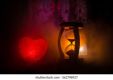 Valentine's Day composition with sweet burning multicolored heart on dark background and Silhouette of Hourglass clock, time and love concept, or love greeting card of heart red green pink yellow