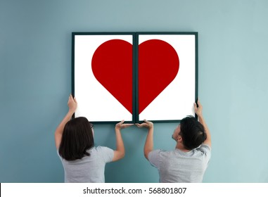 Valentines day concept. Asian couple holding red heart in picture frames. Rear view of lover.