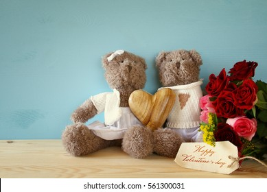Valentines day concept. Couple of cute teddy bears holding a heart, sitting on wooden table