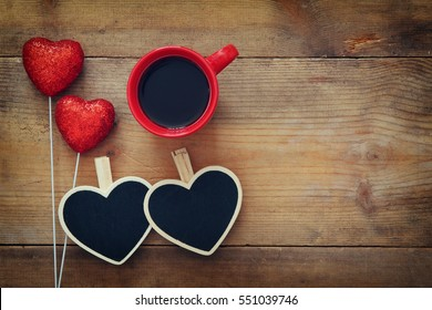 Valentines day concept. Couple of red glitter hearts and chalkboard on wooden background. Flat lay composition